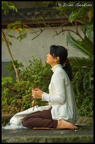 Молящаяся у Дайбуцу (Великого Будды), храм Котоку-ин, Камакура, Япония, Woman prayingat the Great Buddha (Daibutsu) of Kamakura, Kotoku-in Temple, Kamakura, Honshu, Japan